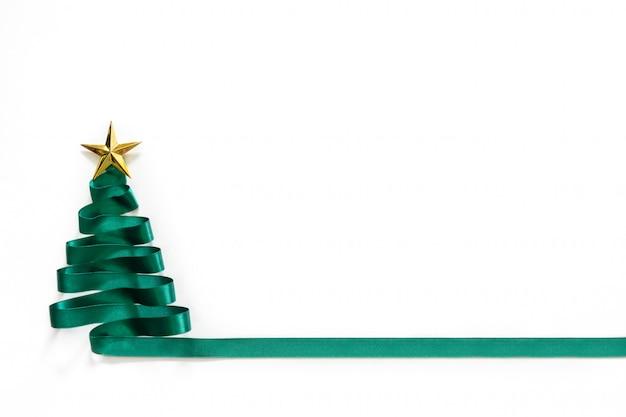 白い背景の上の金の星と緑のリボンから作られたクリスマスツリー