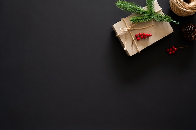 Рождественский подарок на черном фоне с сосновыми ветками, ягодами и веревкой