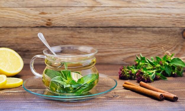 Мятный чай в стеклянной прозрачной чашке на блюдце с лимоном и корицей