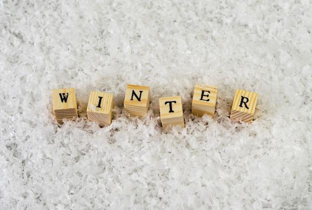 雪の上の木製キューブの文字で作られた冬の言葉