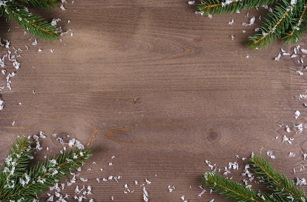 Елочные ветки со снегом на деревянном фоне