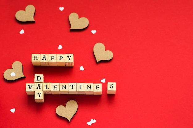 Надпись из деревянных кубиков с днем святого валентина и сердечками