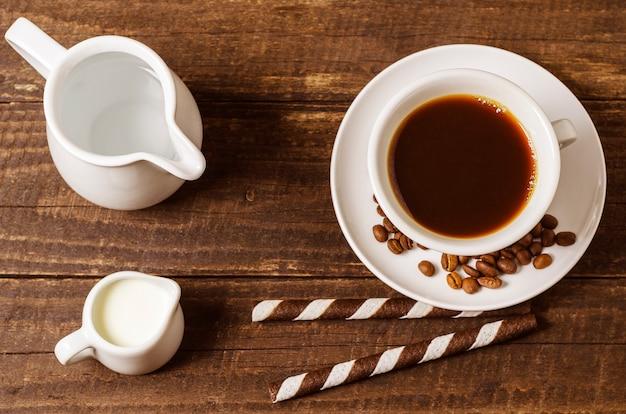 ミルクとウエハーとのコーヒーは、木材の背景にロールします。
