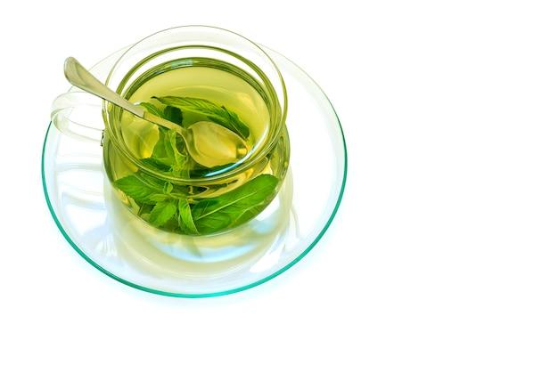 Мятный чай в стеклянной прозрачной чашке на блюдце
