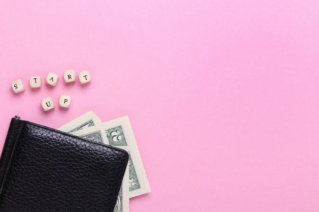 木製の文字の言葉でピンクの背景に黒の財布のクローズアップを開始します。トップビュー、ミニマリズム