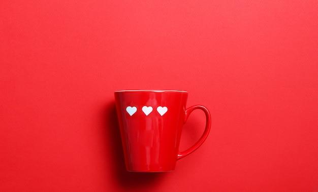 Красная чашка кофе с белыми сердцами на красной стене