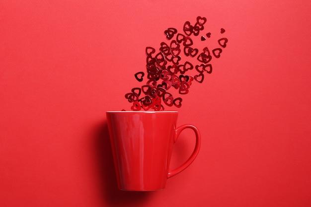 Красная кружка кофе с красным блеском сердца на красной стене. плоская планировочная композиция. романтический, день святого валентина концепции.