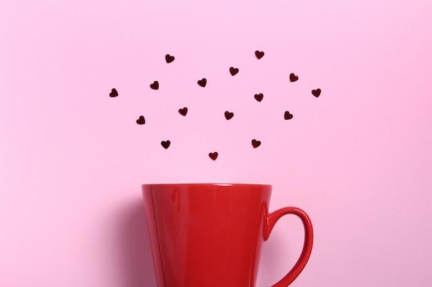 Красная кружка кофе с красным блеском сердца на розовой стене. плоская планировочная композиция. романтический, день святого валентина концепции.