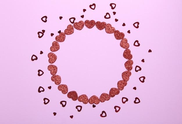 Круг кадр из красного блеска сердца на розовом фоне. романтический, день святого валентина концепция. вид сверху.
