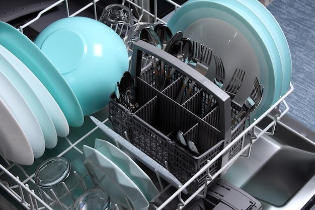Откройте посудомоечную машину с чистой посудой в ней, закройте. очистите тарелки, стаканы, вилки, ложки после мытья в посудомоечной машине. посудомоечная машина после очистки.