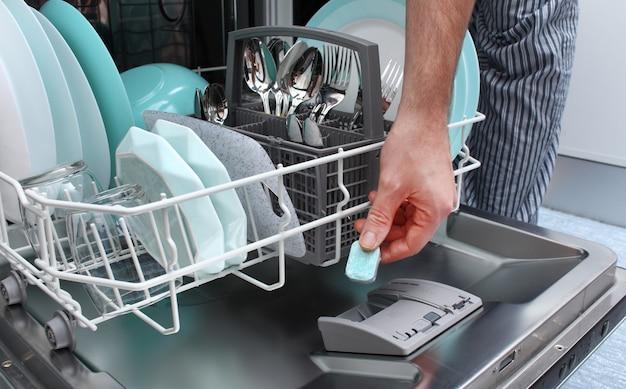 タブレットを食器洗い機に入れます。男は、汚れた皿を洗うためにタブレットを食器洗い機に入れます。
