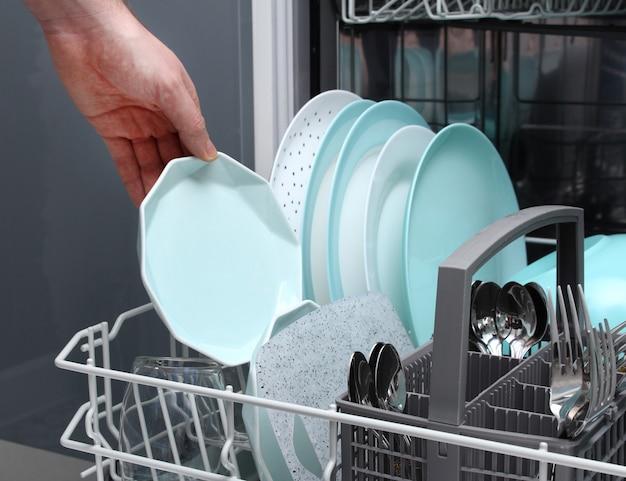 男は台所で食器洗い機を空にします。食器洗い機に皿をロードする男性の手のクローズアップ