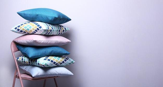 灰色の壁の部屋にスタイリッシュなカラフルな枕。椅子にダークブルー、ピンク、ブルーのクッション。コピースペース、居心地の良い家のコンセプト。