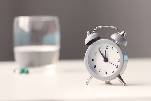 目覚まし時計とベッドサイドテーブルの上の医療薬。ヘルスケアと薬。