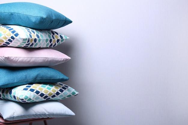 灰色の壁の部屋でスタイリッシュなカラフルな枕のクローズアップ。ダークブルー、ピンク、ブルーのクッションコピースペース、居心地の良いホームコンセプト。