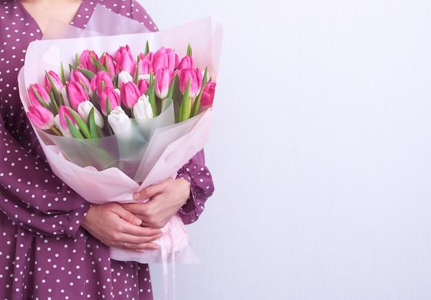 灰色のピンクと白のチューリップの花束を保持している紫色のドレスの若い女性の肖像画。春のグリーティングカード。 。イースター、春の花のコンセプト。母または女性の日。