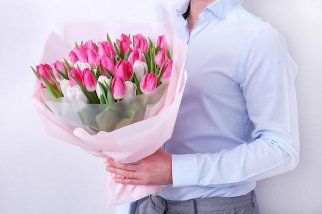 グレーのピンクと白のチューリップの花束を保持している青いシャツの若い男の肖像画。春のグリーティングカード。 。イースター、春の花のコンセプト。母または女性の日。