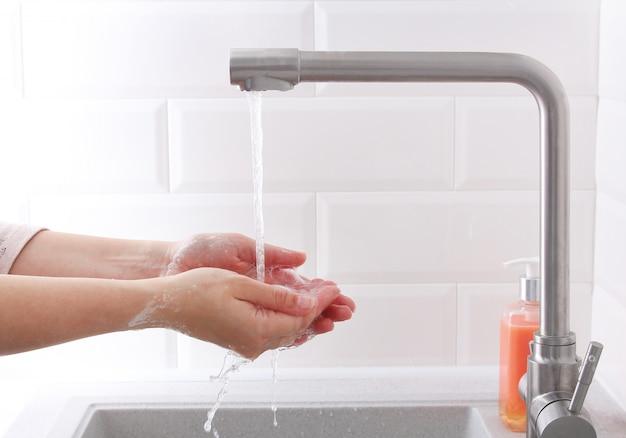 自宅で石鹸で手を洗う女。