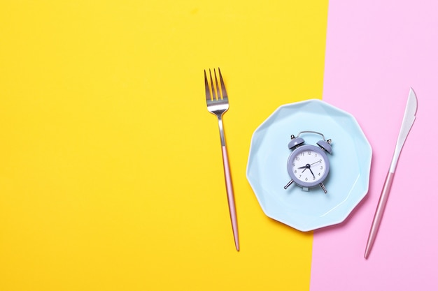 灰色の目覚まし時計、フォークとナイフの黄色とピンクの空の青いプレート。断続的な断食、ランチタイム、ダイエット、減量の概念。平面図、フラットレイアウト、ミニマリズム。