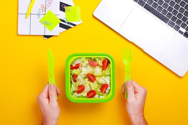 プラスチック容器に食物と一緒に男の手のクローズアップ。仕事中に新鮮なサラダを食べる男。健康食品のコンセプト。平面図、フラット横たわっていた、黄色の背景。仕事場で健康的なスナック。