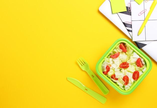 緑色のランチボックスにプラスチックフォークとナイフを職場で新鮮な野菜サラダ。プラスチック製の容器に健康的なスナックのクローズアップ。健康食品のコンセプト。平面図、フラットレイアウト、黄色の背景。