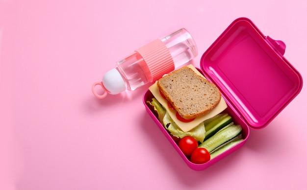 水のボトルとピンクのランチボックスで新鮮なサンドイッチ、ポテト、キュウリ。プラスチック製の容器で健康的なスナックのクローズアップ。健康食品のコンセプト。平面図、フラットレイアウト、ピンクの背景。
