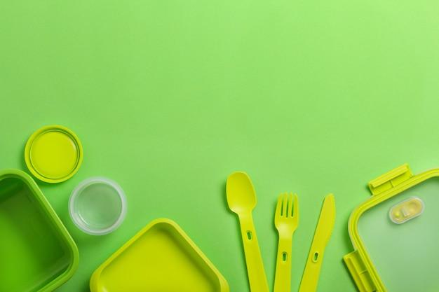 緑色の背景でフォーク、スプーン、ナイフで緑のプラスチック製ランチボックス。平面図、フラットが横たわっていた。学校やオフィスの食品容器。コピースペース。