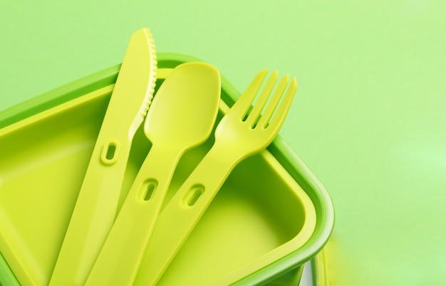 緑の背景に緑のプラスチック製ランチボックスのクローズアップ。プラスチックのフォーク、スプーン、ナイフ。コピースペース。学校やオフィスの食品容器。
