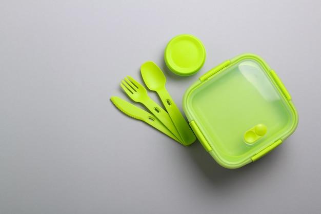 灰色の背景にフォーク、スプーン、ナイフで緑のプラスチック製ランチボックス。平面図、フラットが横たわっていた。学校やオフィスの食品容器。コピースペース。