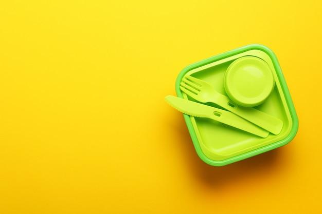 黄色の背景にフォーク、スプーン、ナイフで緑のプラスチック製ランチボックス。平面図、フラットが横たわっていた。学校やオフィスの食品容器。コピースペース。