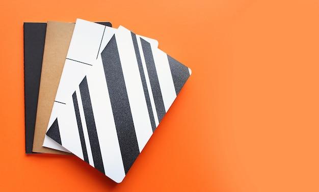 学校コンセプト、学用品、カラフルなノートブックの明るいオレンジ色の背景のトップビューに戻る