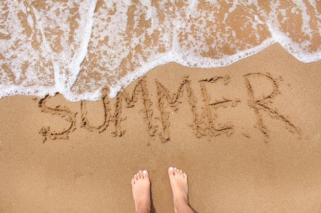 Взгляд сверху женских ног стоя на песке пляжа с приходить волнового движения.