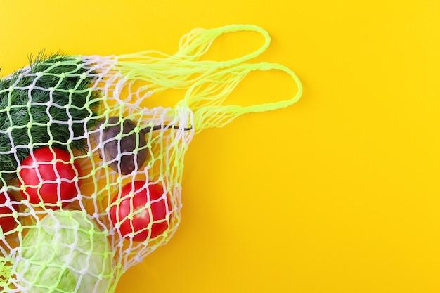 Многоразовая белая сетчатая сумка с фруктами и овощами: помидоры, капуста, свекла, укроп, персики.