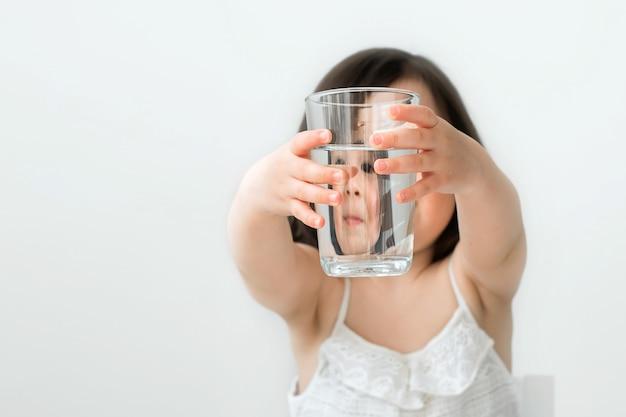 女の子は彼女が水を飲むことを私たちに示しています