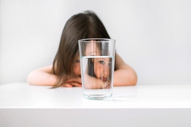 その少女はテーブルの動揺に座る。彼女は水を飲みたくないので悲しいです。