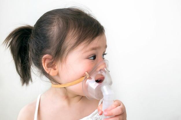 Маленькая девочка лечит кашель и насморк. девушка сидит с вдохом