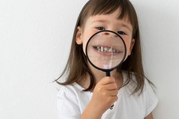 小さな女の子は彼女の歯を示しています