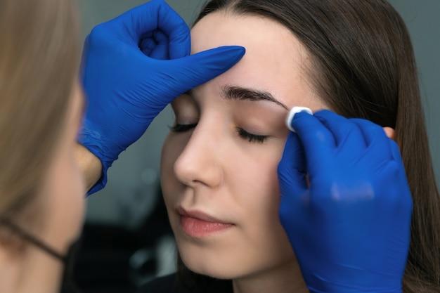 若い女性は、美容サロンで彼女の眉毛をピンセットします。