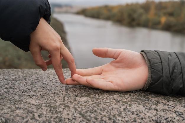 Влюбленные касаются друг друга пальцами.