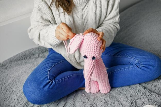 女の子はピンクの糸のおもちゃをニット