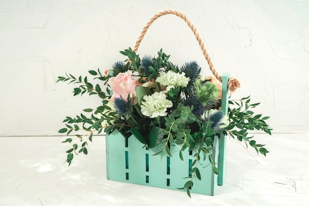 花束が付いたかわいいターコイズ色のバスケット。レストランの装飾のための結婚式の花