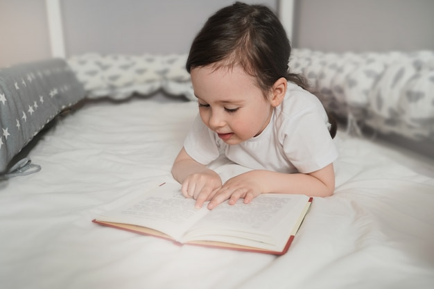 子供はベッドで寝る前に本を読みます。女の子はカバーの下に隠れて読みました。ピンクの毛布に隠れている幼児。