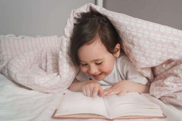 Ребенок читает книгу перед сном в своей постели. девушка спряталась под одеялом и читает. малыш прячется в розовом одеяле.