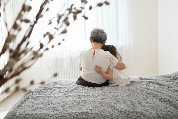 祖母と孫娘が座って抱きしめます。