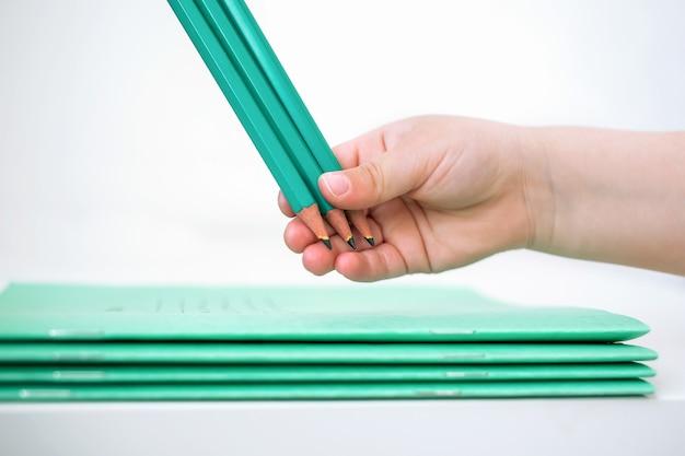 子供の手は学校のノートの近くに鉛筆を持っています。