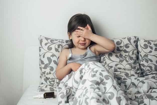その少女は病気になった。子供は熱があります。温度計をクローズアップ。