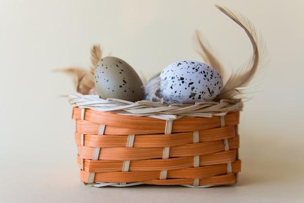 Пасхальный фон с яйцами и перьями в корзине