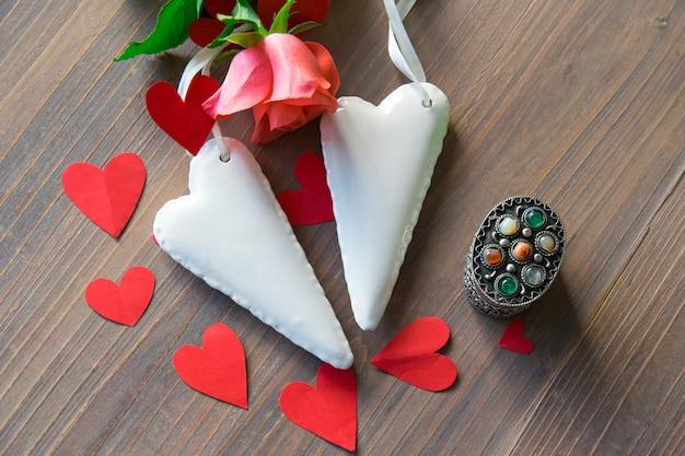 Фарфоровые белые сердечки с розовой розой на столе.