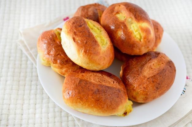 白いプレート上の酵母パン。ジャガイモとパイ。おいしい朝食、自家製料理。ベーキング、生地。