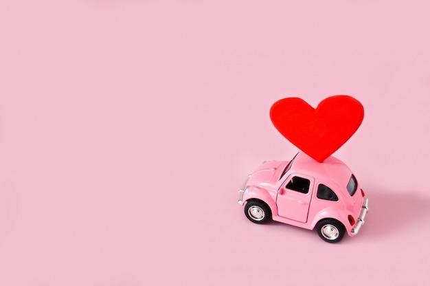 Розовый ретро игрушечный автомобиль с красным сердцем